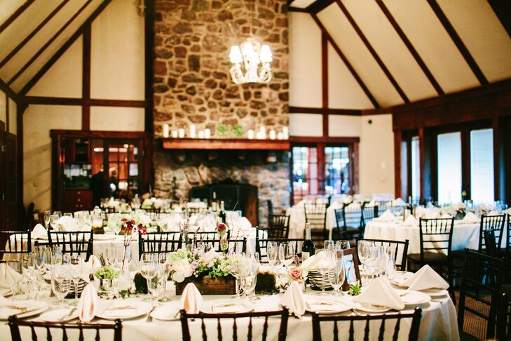 The tables in the reception room were oblong, so Elaine and her florist agreed that low-yet-long centerpieces would be the best way to adorn them. The arrangements of succulents, roses, moss and lavender were placed inside wooden flower boxes and surrounded by candles. Tables were set with simple white linens.