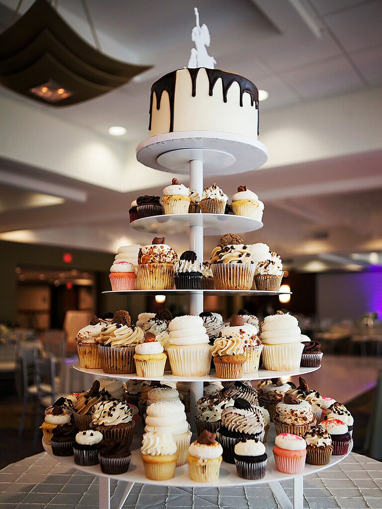 Tiered wedding cake display with cupcakes and a drip cake