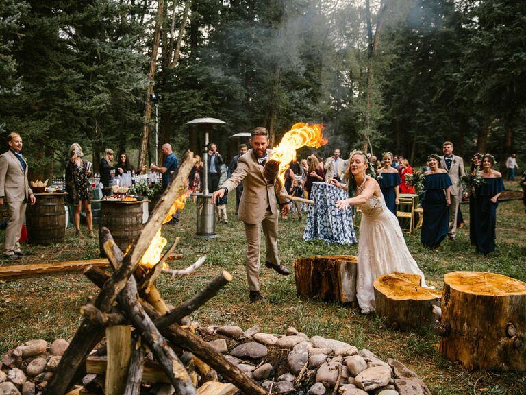 Bride and groom lighting bonfire during wedding unity ceremony