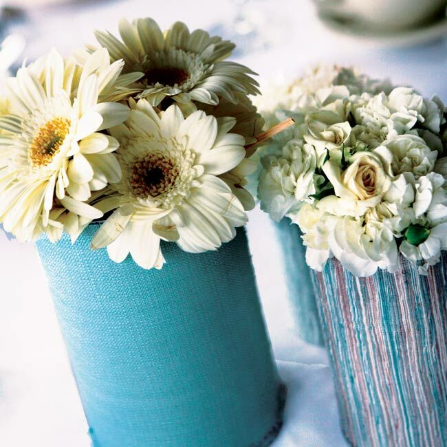 Small centerpieces of white blooms in vases covered with light blue tweed.