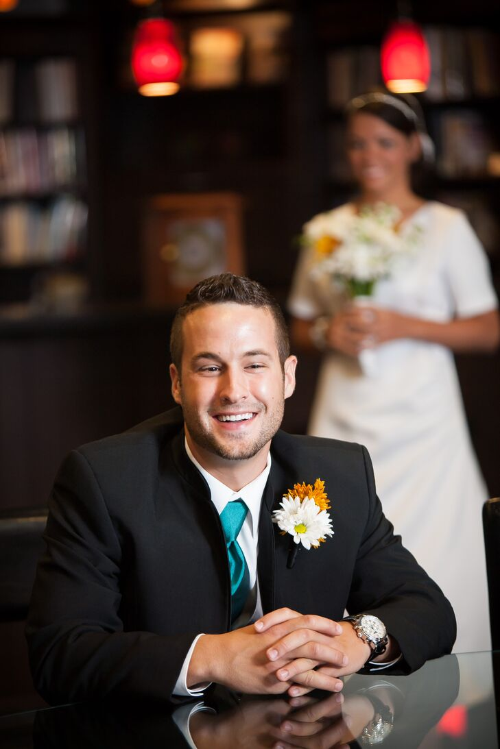 The groom and his groomsmen wore black tuxedoes with teal ties for a bright pop of color. They also sore yellow and white daisy boutonnieres to match the bouquets.