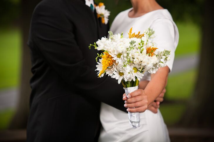 LeAnna carried a natural-looking white and yellow bouquet featuring beautiful daisies. The bouquet was wrapped in a swatch of satin that was embellished with rhinestones.