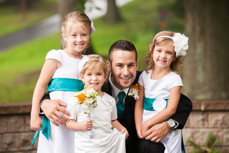 The flower girls wore short sleeve dresses with teal sashes to match the groomsmen's ties. They also wore white floral hair accessories to tie into the daisy flower arrangements.