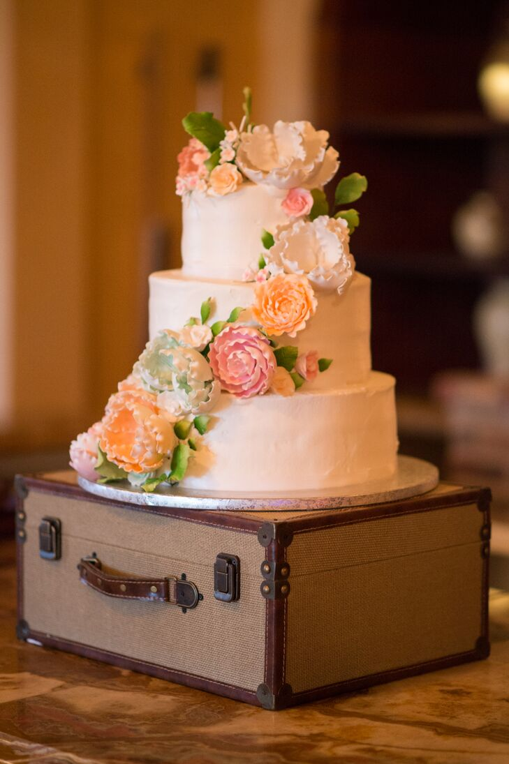 The couple served miniature cheesecakes as well as a traditional wedding cake for dessert. The three-tiered buttercream frosted confection included red velvet, chocolate and vanilla cake with Italian rum or hazelnut cream filling between each layer. Lora personally added gum paste flowers colored with peach, pink and green edible dusting powder, she says.
