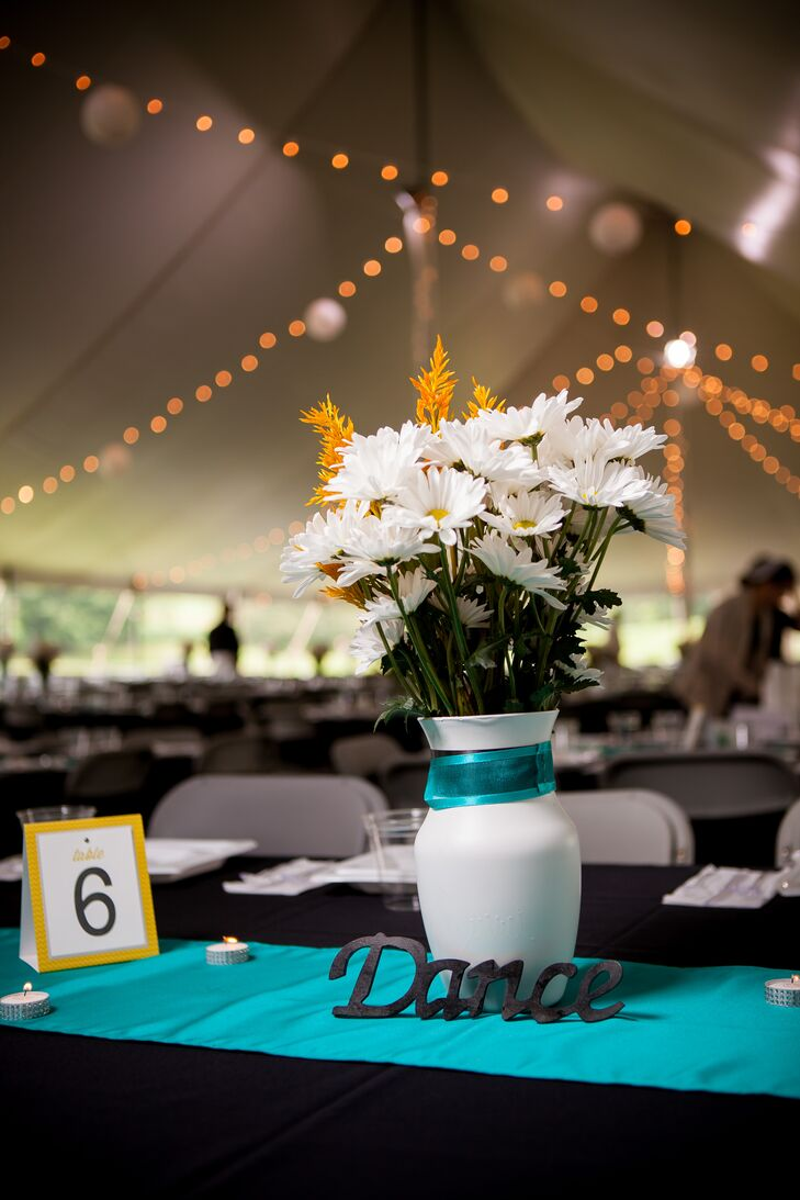 Centerpieces incorporated white vases filled with white and yellow daisies and painted wooded signs with simple expressions. Teal table  runners contrasted with the bright yellow table numbers and warm yellow string lights to match the color scheme.
