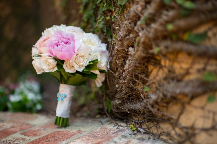 Lora chose peach and white rose bouquet accented with pink and white peonies. It was wrapped with ivory ribbon and a small blue ribbon pin.