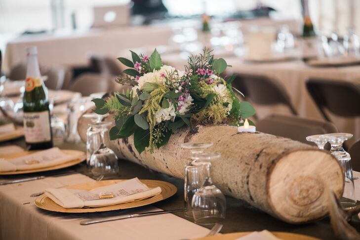 """To weave in a hint of rustic, woodland flair, Julia and Matt displayed the centerpieces—bountiful bouquets of white hydrangeas, ferns, purple wax flowers and eucalyptus—in fallen logs sourced from the nearby woods. """"Matt is a hunter, and I really liked the idea of incorporating deer antlers into our decor by having them wrap around the sparkling juice bottles on the table,"""" Julia says."""