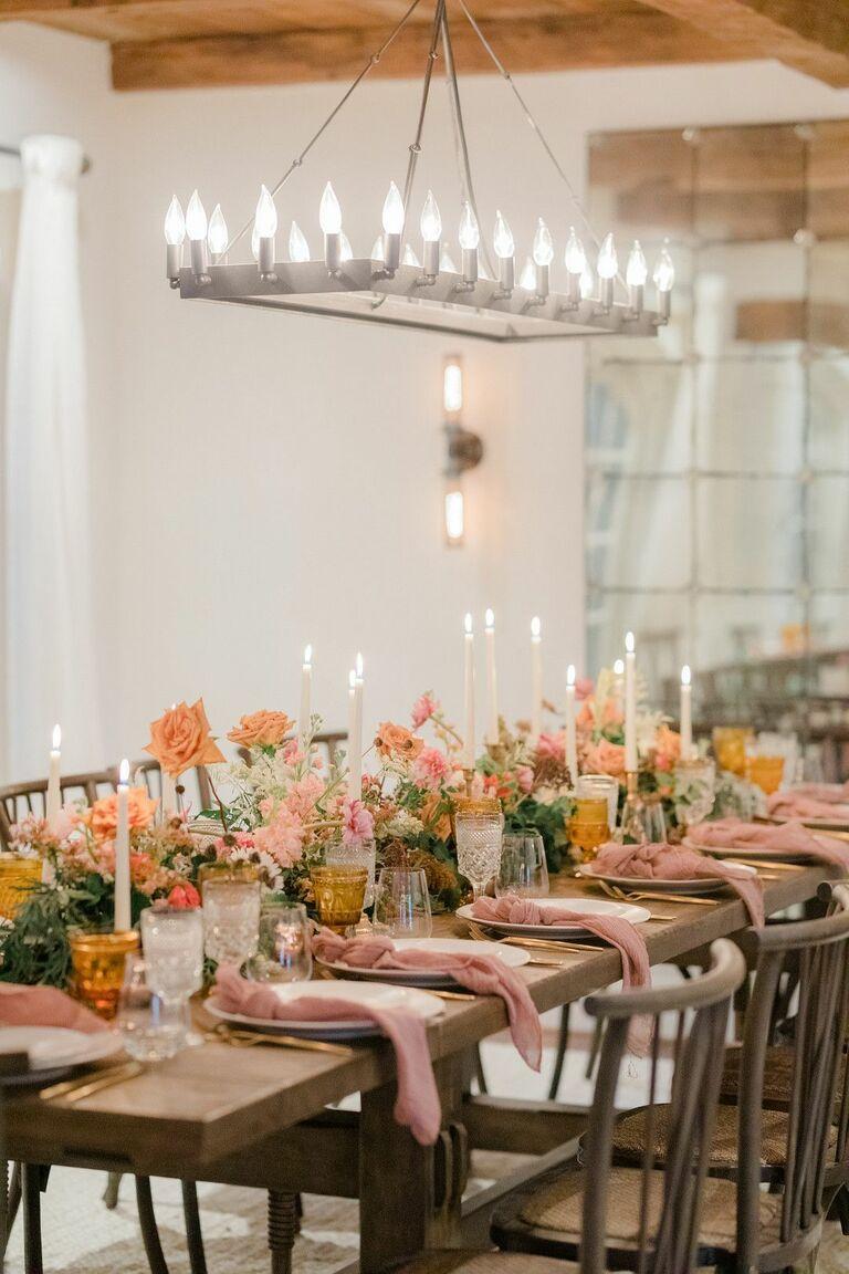 Farm table with orange flowers underneath chandelier