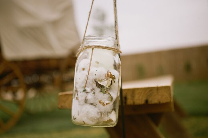 Mason jars filled with cotton decorated every aspect of the wedding, from the ceremony as aisle and arbor decorations to the reception table centerpieces.