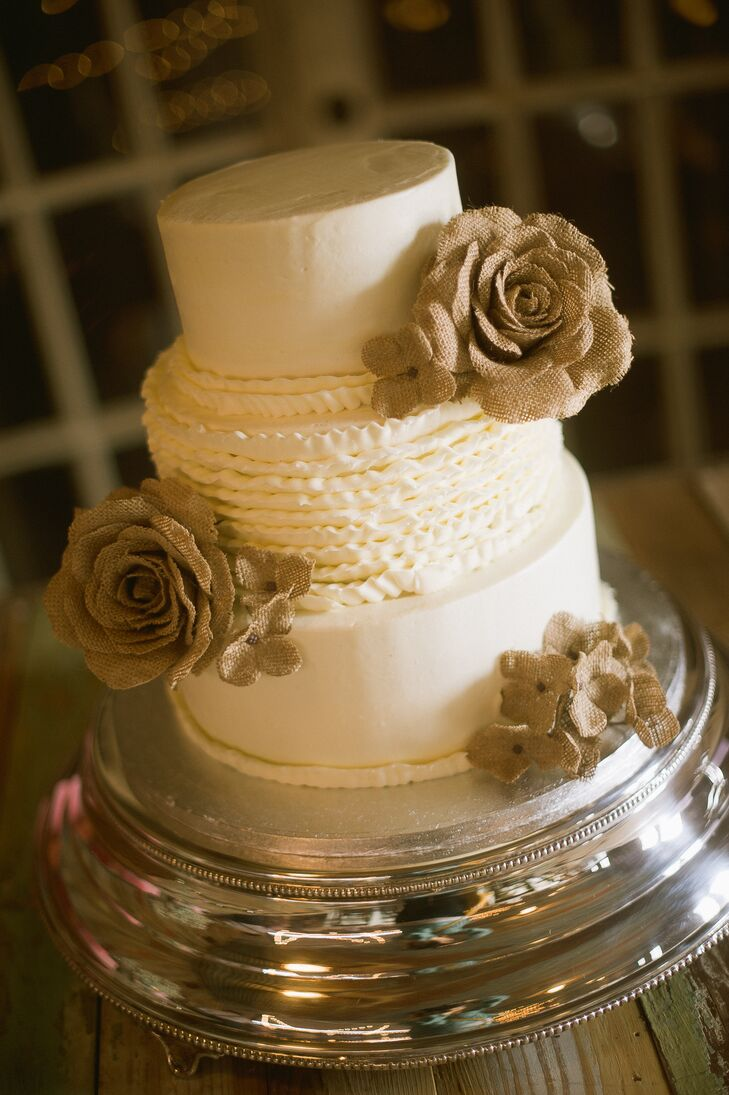 The bride's cake was white and decorated with burlap flowers for a rustic look.