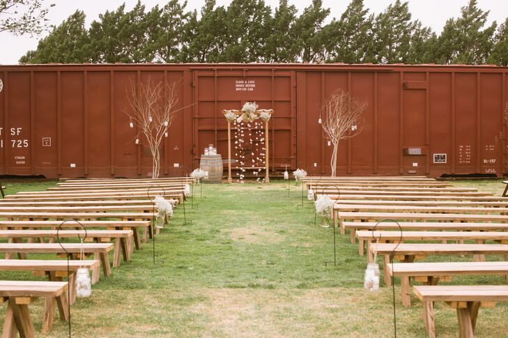 """The ceremony took place in front of a vintage rail car. """"It was such a unique venue that allowed us to have an outdoor ceremony but also host the reception in a beautiful barn made out of refurbished wood."""