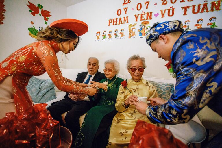 Couple serving tea to elders during Vietnamese wedding ceremony
