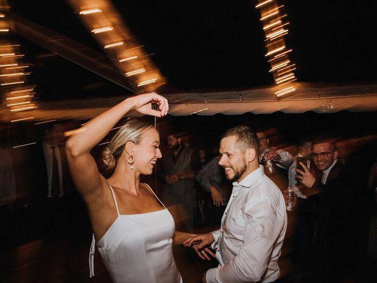 Bride in '90s slip wedding dress dancing with groom at reception