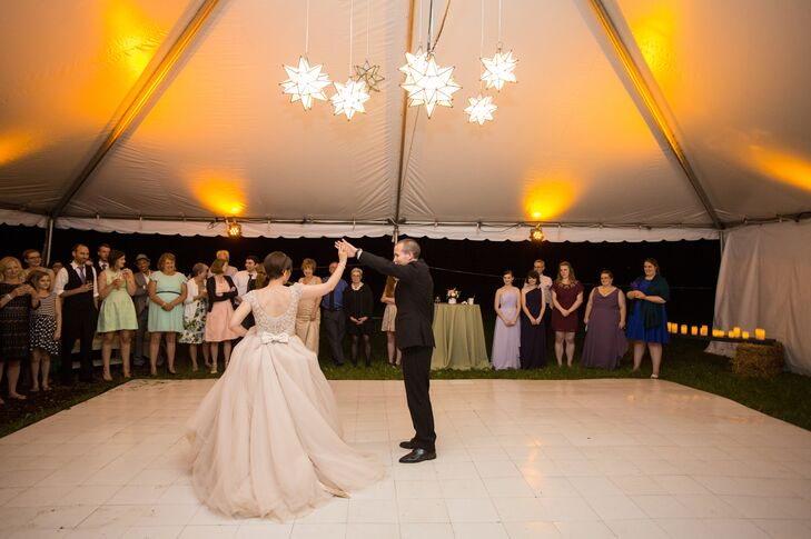 Haley and Michael set up a white tent to connect the barn, where everyone had dinner, to the outdoor dance floor. They wanted to create lots of space on the family farm for guests to move and have fun. The newlyweds started the dance party with their first dance under the modern, geometric hanging star chandelier.
