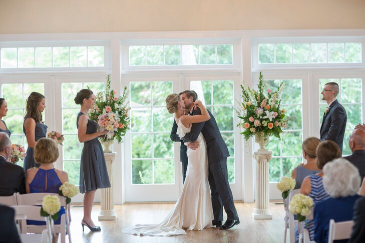 Decor at the ceremony featured pedestal flower arrangements of white delphinium, peach hyacinth, peach ranucnulses, pink roses and white lilies placed on white pillars at the altar.