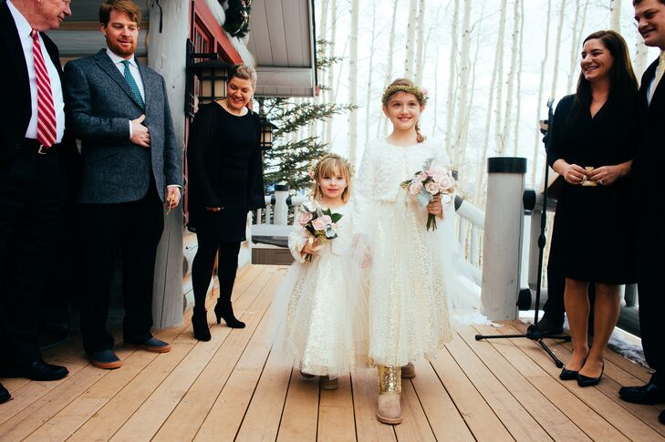 The flower girls wore sparkly gold dresses with a light tulle overlay on the skirt. They completed their look with rosette-patterned white sweaters since the winter wedding was outside. They carried small rose and lamb's ear bouquets and wore flower crowns that matched the bride.