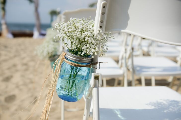Blue mason jars filled with baby's breath lined the ceremony aisle.