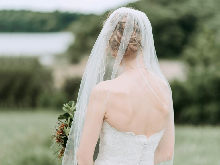 bride in a veil facing away from the camera