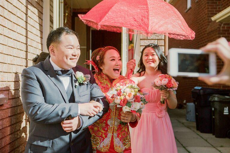 Bride walking under red fan during Chinese wedding