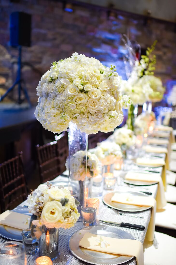 The long head table was lined with an array of flower arrangements, including tall glass pilsner vases that were topped with dome-shape bouquets of ivory hydrangeas and roses.