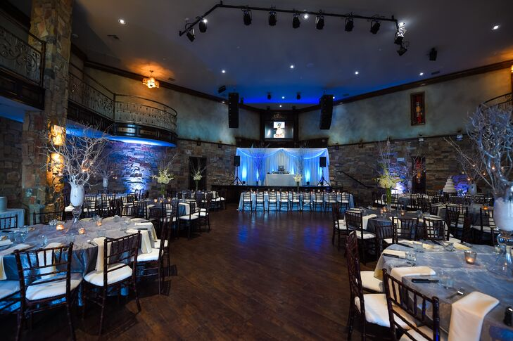 The reception featured blue uplighting to add to the winter theme. The space was arranged with black chiavari chairs and round dining tables covered in sparkly silver linens.