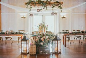 Sweetheart Table Surrounded by Rustic Décor, Flowers and Hanging Branch Chandelier