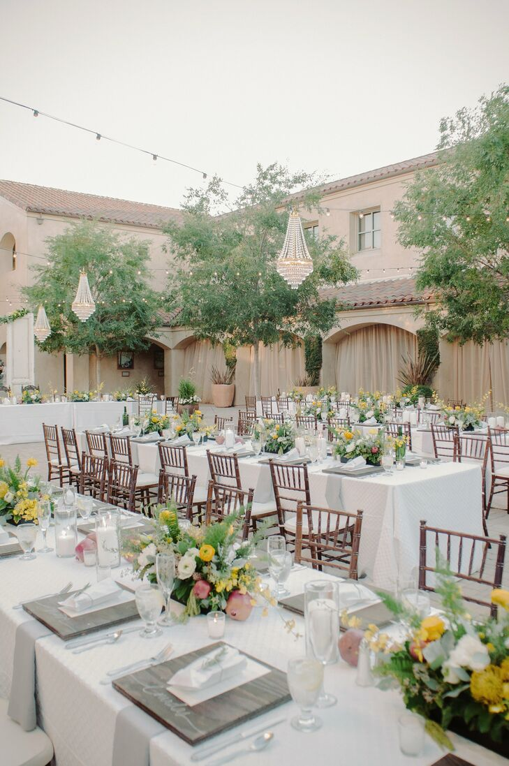 The reception took place outdoors in a courtyard at Serra Plaza. Chandeliers hung over long farm tables set with classic white linens, wood accents, pomegranates and colorful rustic floral arrangements, that felt elegant and sophisticated while also giving off the natural, organic vibe the couple was trying to achieve.