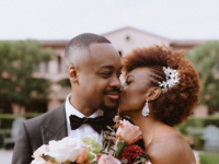 Couple holding bouquet and sharing kiss