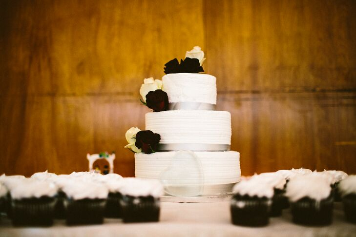 Kelli and Adrian's classic, elegant three-tiered wedding cake was topped with dramatic, dark crimson blossoms and surrounded by cupcakes, which guests were more than happy to grab.