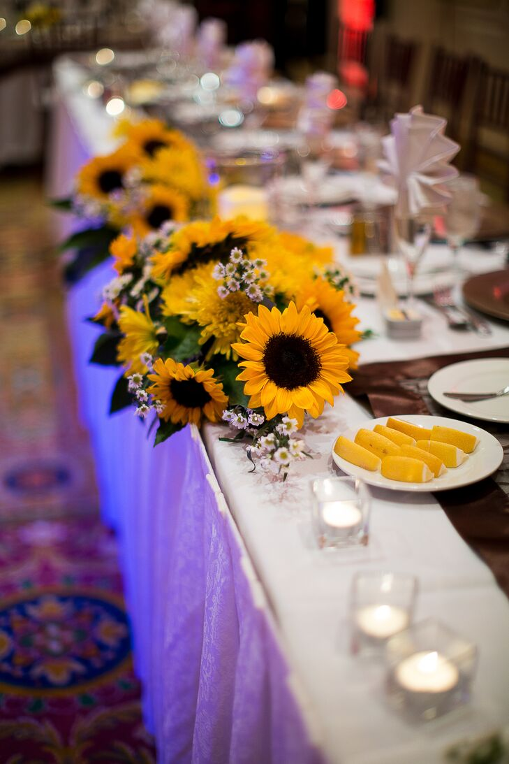 Flowers at the reception included arrangements sunflowers, small white daisies and bright yellow spider chrysanthemums at the head table.