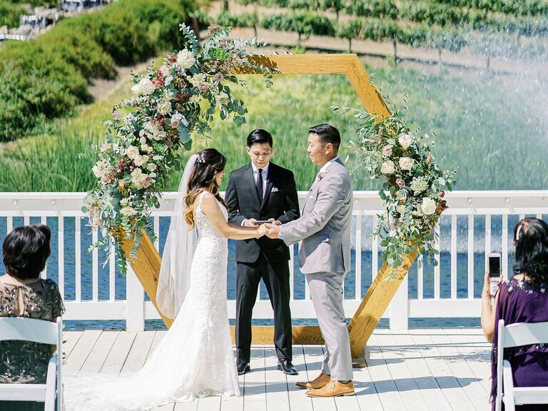 wedding officiant couple smiling holding hands outside
