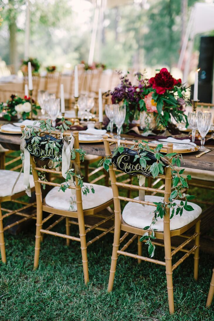 "Unlimited Party & Event Rental provided gold chiavari chairs to contrast the rustic wooden farm dining tables. Sprigs of greenery decorated the black and gold ""bride"" and ""groom"" signs on the backs of Madelyn and Joseph's chairs."