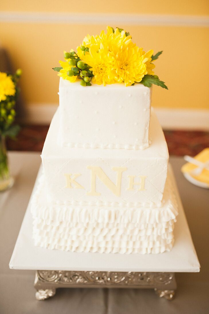 """Every tier of their cake was completely different, inside and out. Sweet Designs Kitchen baked each one with chocolate, Key lime or strawberry cake, then covered the confection in white fondant. White Swiss dots or a quilted pattern with the couple's yellow monogram decorated the top two tiers. """"Our bottom layer was ruffled to resemble the bottom of my wedding gown,"""" says Kimberlee. Adding an extra pop of color, the couple personalized their dessert even more with a topper of yellow chrysanthemums and green hypericum."""