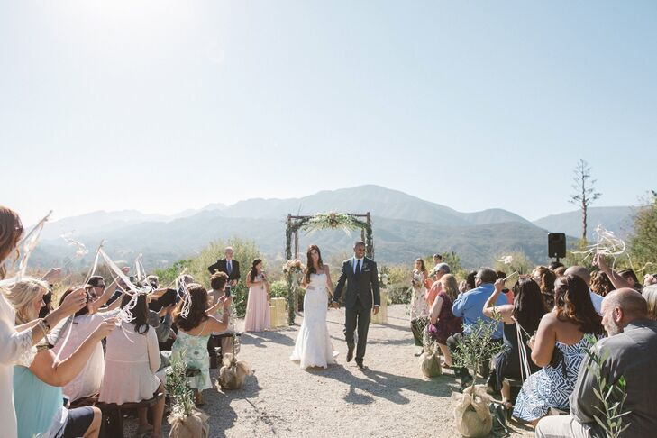 "Tracy and Michael's guests watched the couple wed from their wooden benches covered with soft throw blankets. ""The backdrop for the ceremony was stunning by itself,"" Tracy says. ""The vast valley behind the ceremony site was endless and the beautiful landscaping  just made it more dreamy."""