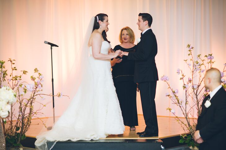 To make the Gershon Fox Ballroom Atrium's their own, Pamela and Dan covered their ceremony in romantic decor. With the help of Amy Champagne Events, they covered the backdrop in blush draped fabric and white uplighting. Fleurescent heightened the atmosphere with cherry blossoms on either side of their stage.