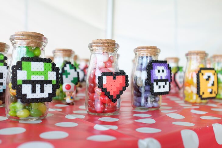 Small clear jars with colorful jellybeans and classic power-up perlers glued on the outside of the jar were given to guests as a unique, sweet treat.