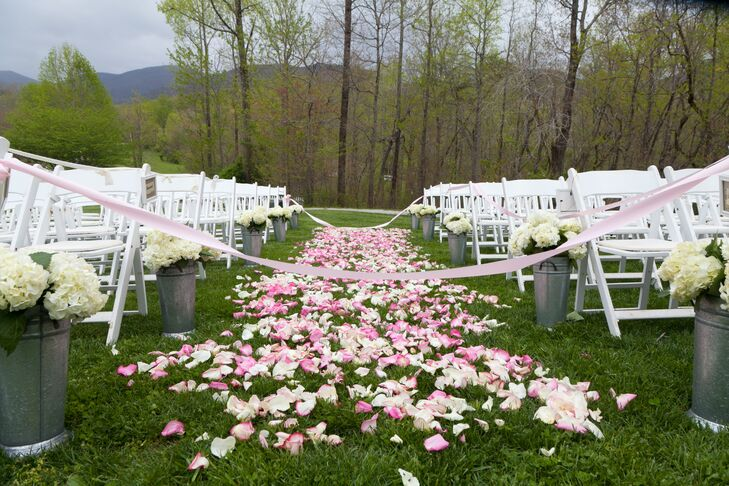 The couple walked down a homemade aisle of pale pink rose petals before exchanging vows during an outdoor ceremony in front of the ruins.
