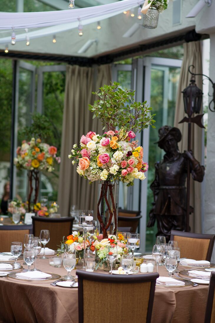 The reception tables were covered in tall glass vases filled with wood and topped with roses, dahlias and peonies for a lush, garden feel.