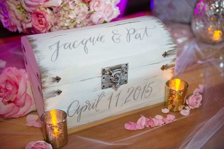 A custom white treasure box with the couple's names and the wedding date painted on it was used to collect cards from guests.