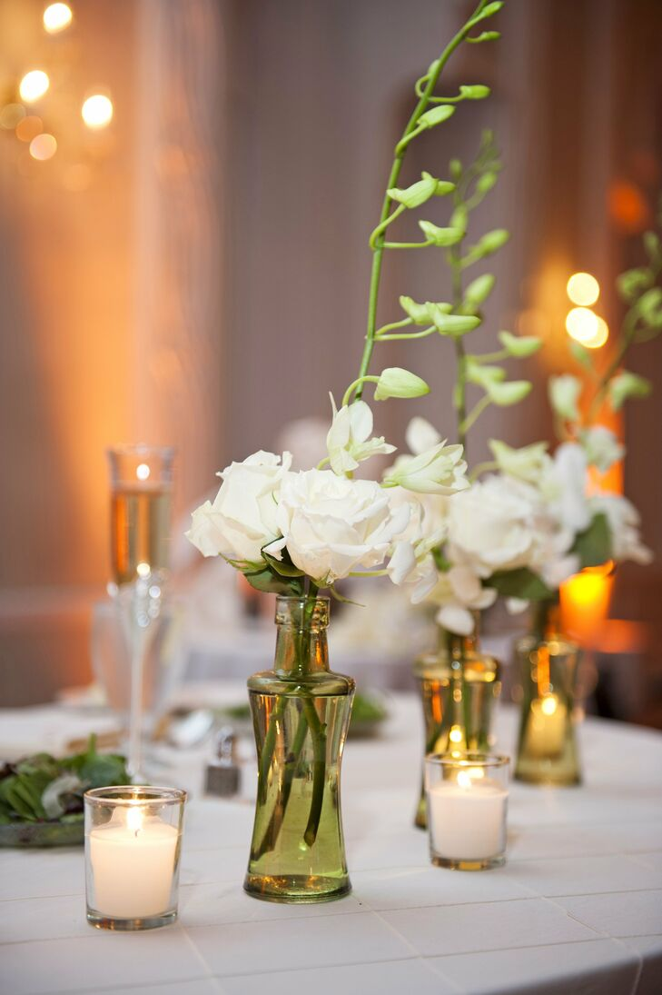 The couple filled green glass vases with white roses to decorate the tables along with candles.
