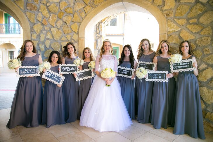 Courtney's bridesmaids wore floor-length Alfred Angelo dresses in charcoal gray. They styled their hair down for a relaxed look. For a cute photo-op, they wrote how they met Courtney on chalkboard signs.
