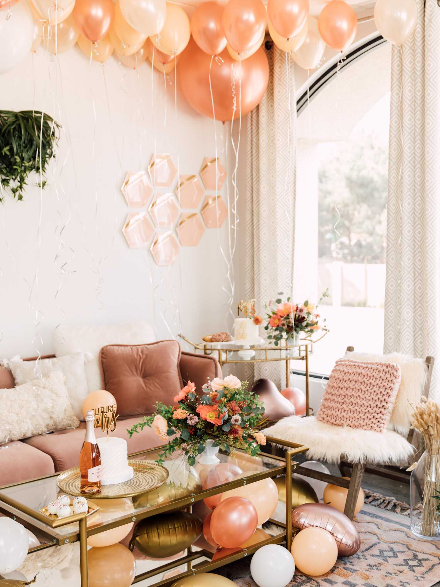 Peach and gold balloons covering the ceiling of a party