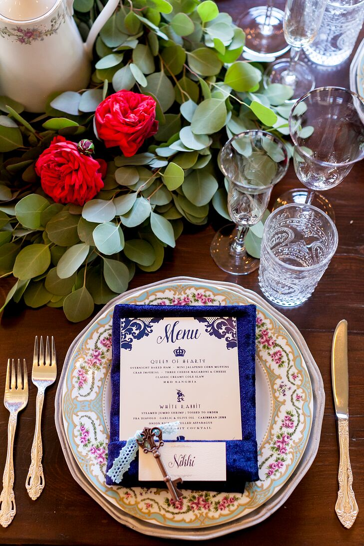 As a nod to the Mad Hatter's tea party, the tables were dressed with vintage-inspired glassware and mismatched floral china, giving the tablescapes an elegant, feminine vibe. Dark navy napkins popped against the pastel dinnerware, with theme-inspired menu cards tucked into each one.