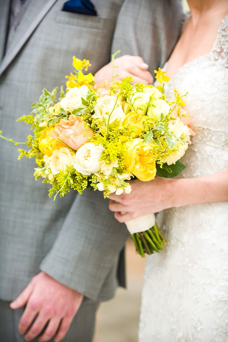 The bride carried a bright bouquet of yellow astilbe and white and yellow roses. The yellow astilbe gave the bouquet a just-picked wildflower look and matched the yellow and navy blue wedding color palette perfectly.