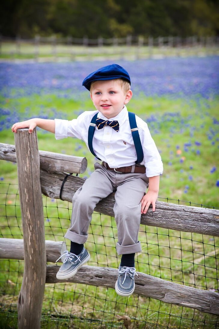 An adorable ring bearer wore a white buttoned shirt paired with gray slacks, navy suspenders and a yellow and navy bow tie to match the groomsmen.