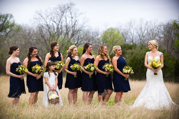 Lacy's bridesmaids wore navy chiffon dresses. Each bridesmaid stood out by wearing a slightly different neckline and they paired the dresses with nude heels. Each bridesmaid carried a yellow bouquet.
