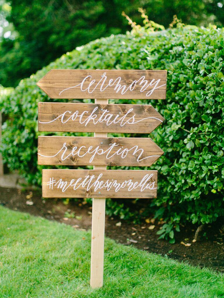 Wood calligraphy signage at wedding with custom hashtag