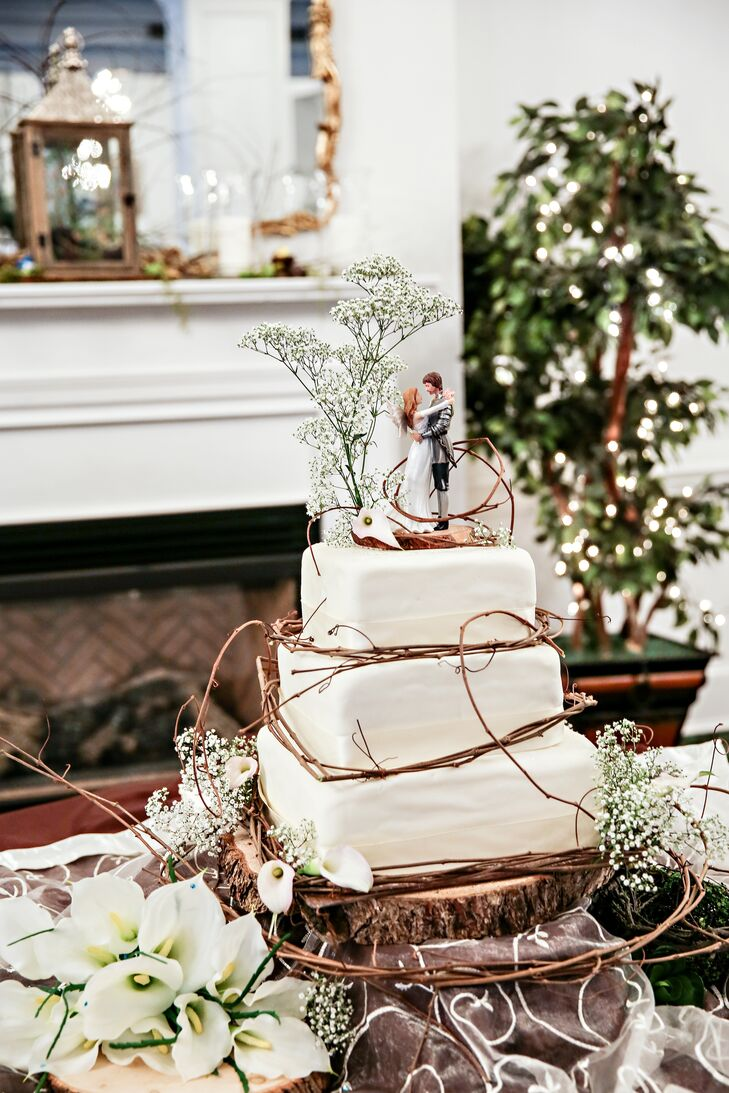 A medieval fantasy knight and angel figurine topped the three-tiered square cake with twig and moss accents.