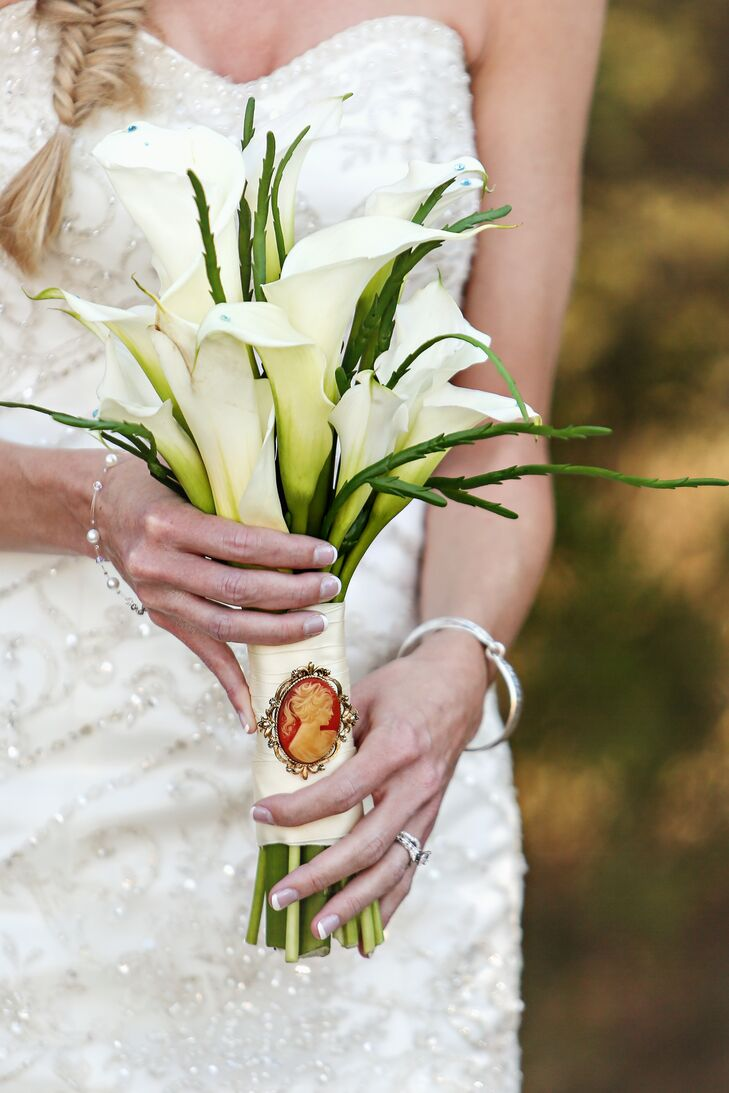 Ashley carried a white calla lily bouquet with teal gems around the petals and an ivory wrap.