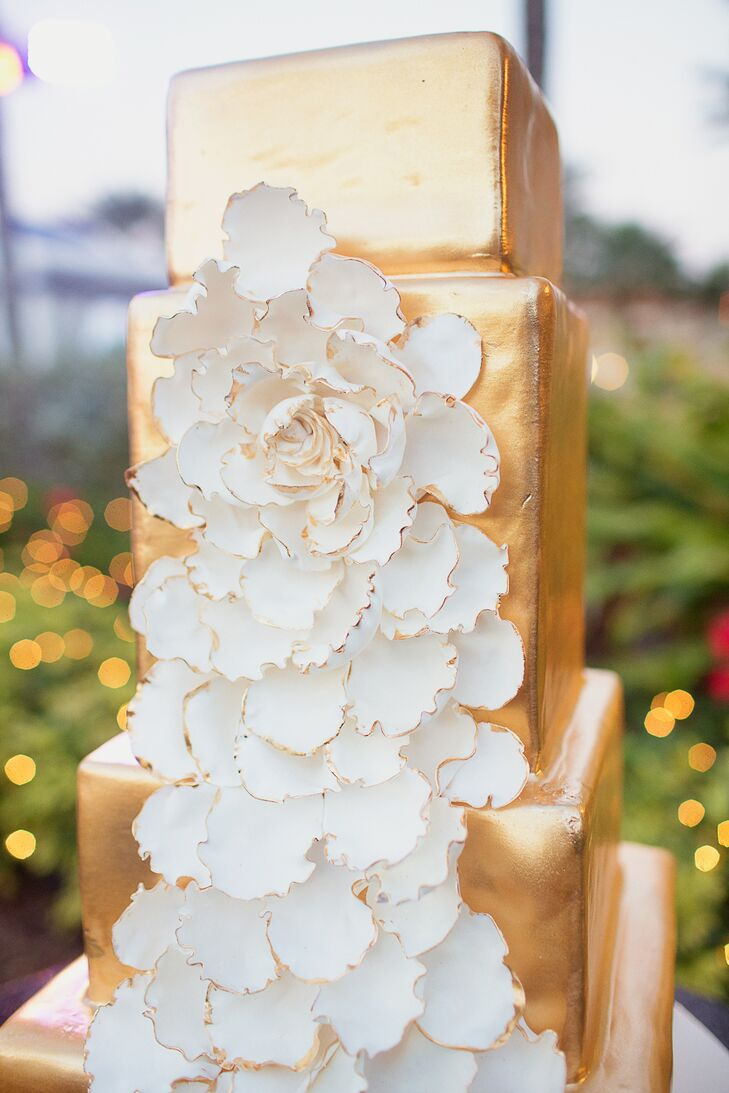 The couple treated their guests to a bold four-tier gold confection decorated with a large white composite flower.